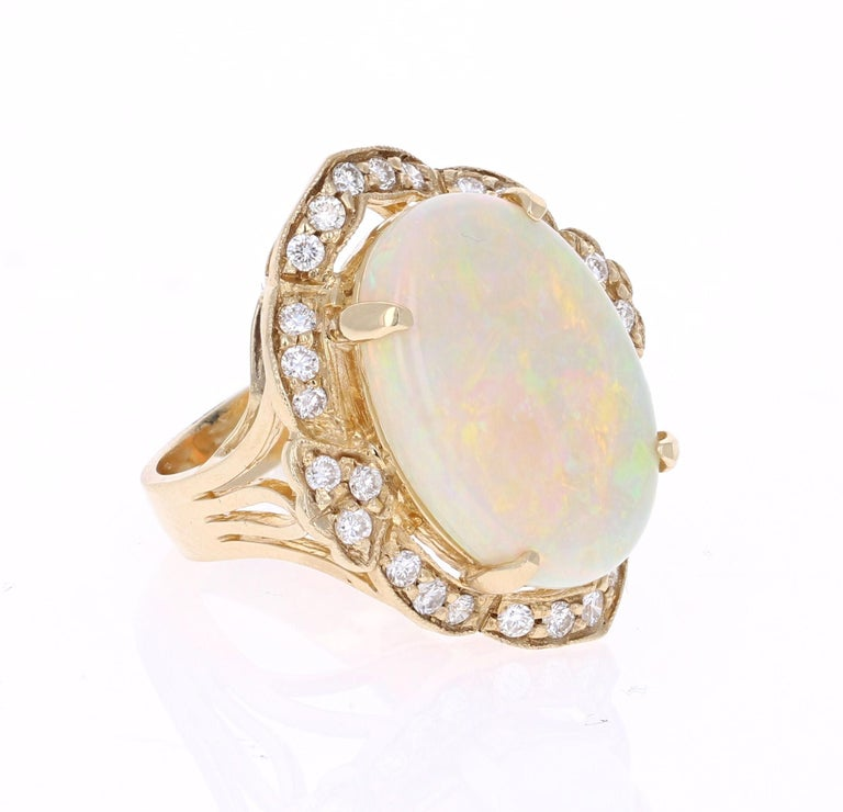 This ring has a 9.18 Carat Opal that is curated in a unique Victorian-Inspired setting 14 Karat Yellow Gold. The setting is adorned with 28 Round Cut Diamonds that weigh 0.84 Carats. The total carat weight of the ring is 9.93 Carats.  The Opal
