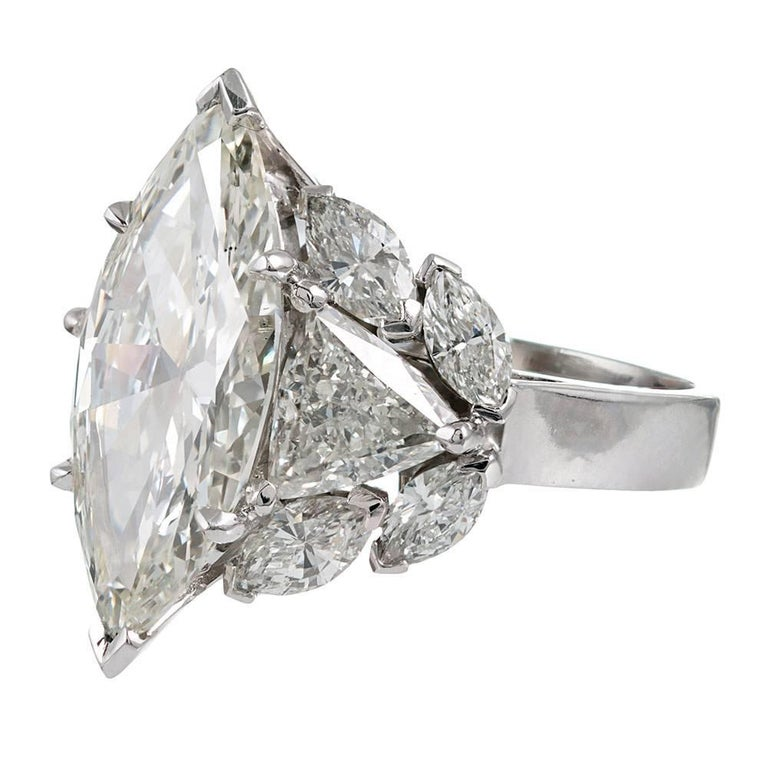 An impressive cluster, the design centered upon a 5.95 carat marquis diamond, flanked by trillion diamonds and additional marquis diamonds dancing about the perimeter. The major diamond is described by GIA as exhibiting color with Vs2 clarity and
