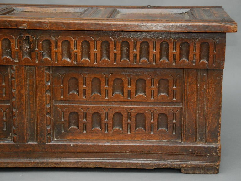 A 17th century oak chest with a triple paneled top having incised lozenges and the interior with remains of a shelf, the frieze and twin paneled front with arcaded carvings. This has a gorgeous patina!