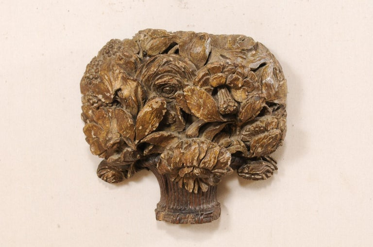 A French carved-wood bouquet wall plaque from the 18th century. This antique wall ornament from France has been fashioned out of a single piece of wood and features a bouquet-shaped body comprised of three-dimensional, hand carved flowers with roses