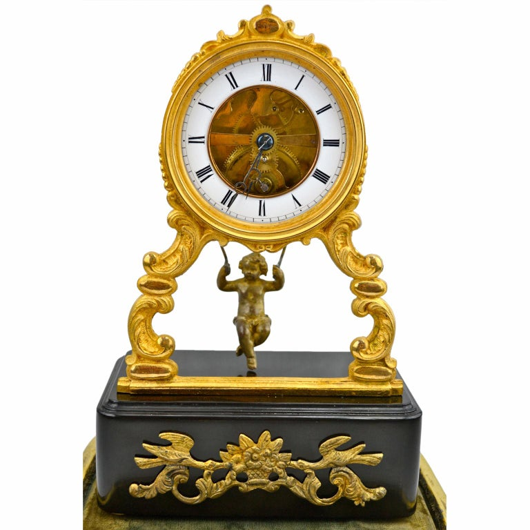 A late 19th century French swinging putto 'mystery' clock. The clock drum has a gilded bronze bezel and is supported on two scrolling front legs which are supported on a rectangular ebonized base with a front gilded mount. The white enamel chapter