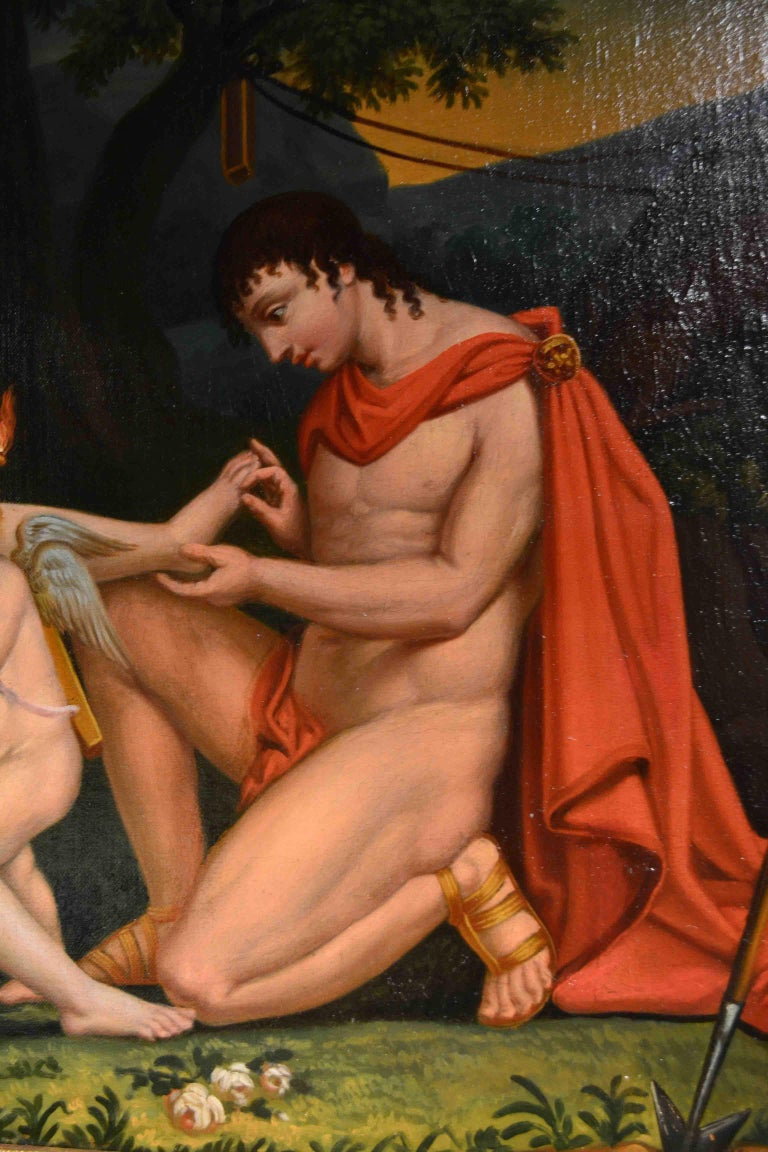 A 19th century neoclassical genre painting showing a draped Apollo kneeling in front of seated Diana pulling a thorn out of her foot, between them cupid is standing holding a flambeau, The unsigned painting which has been recently restored, was