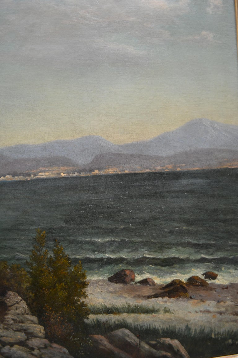 A large oil on canvas of a Northern Italian lake landscape showing part of the shoreline of Lake Como with a tiny village on a peninsula jutting out the lake as it was in the late 19th century by Austrian landscape artist Karl Kaufmann. Signed