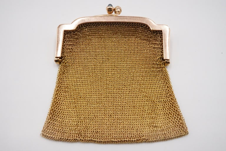 A 1900s Cartier sapphire and 14ct gold mesh bag features kiss lock fastener which has 2 sapphires the hallmarks reads '14K', ' Cartier' and '723'.  W:5.2cm H:6.1cm D:0.57cm Weight: 30.66g