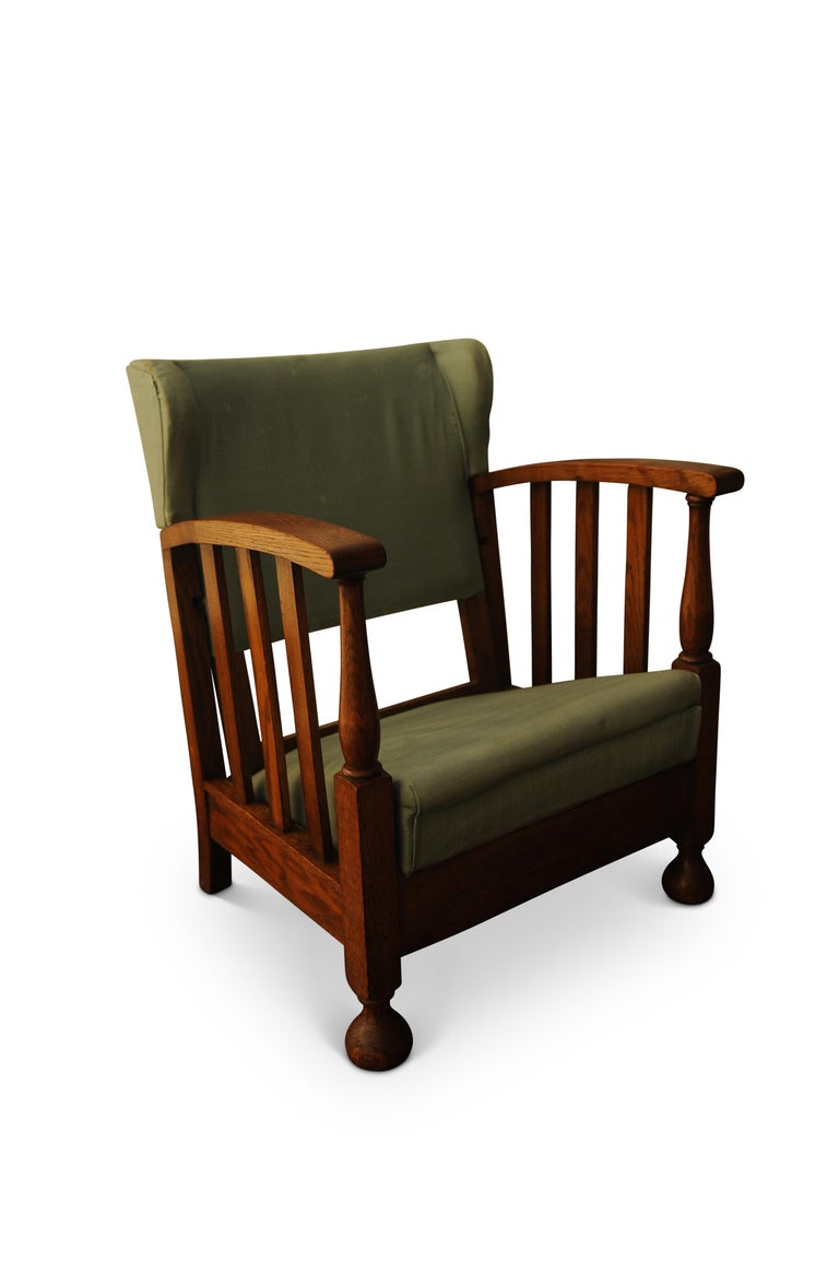 Art Deco oak open reclining armchair with green upholstery.  A lovely little piece of furniture from the Art Deco, Arts & Crafts Era of England 1920s. All in the original condition with reclining mechanism working. Includes a patent no. of