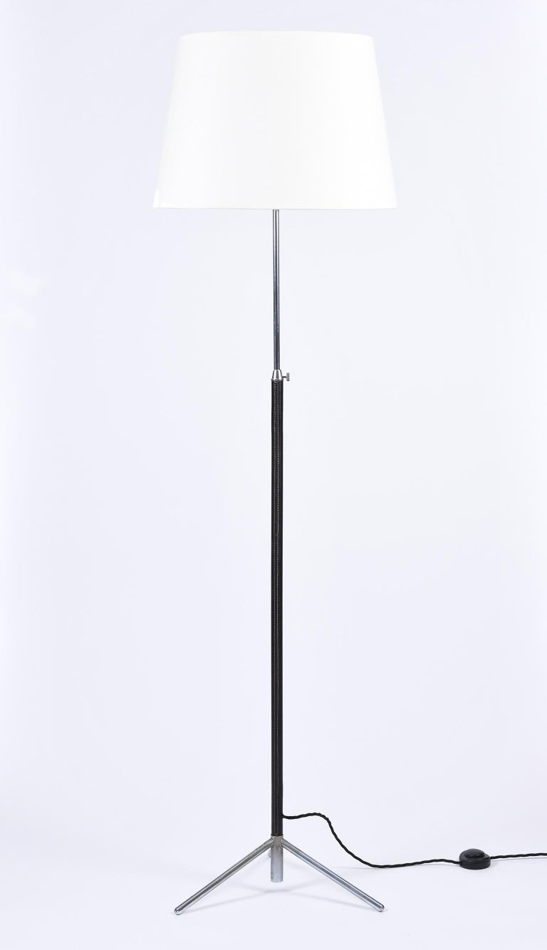 A saddle stitched black leather and nickel plated brass tripod floor lamp, in the manner of Jacques Adnet with a telescopic stem and a bespoke ivory fabric tapered shade France, circa 1950.