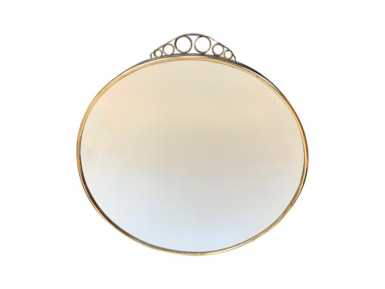 A 1950s Italian circular mirror with beveled glass with a brass frame and top scrolling detail.