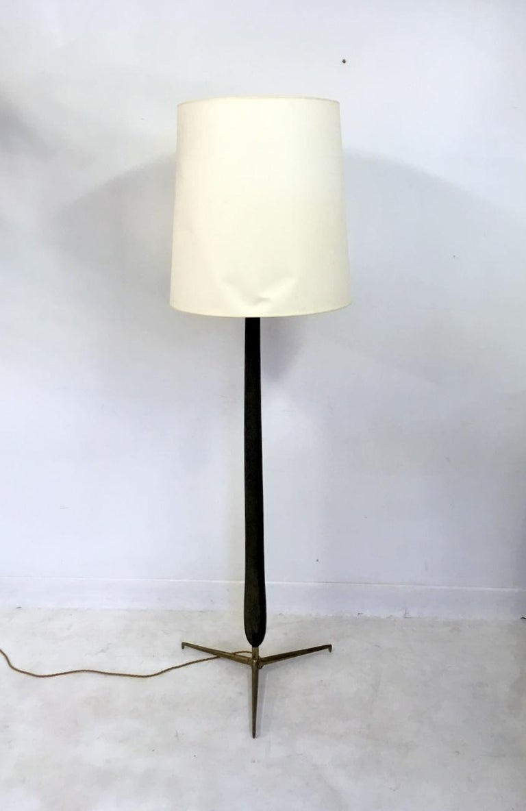 A floor lamp Stained wooden stem Brass three prong base White metal diffuser Comes with large shade too Rewired Italy, 1950s.