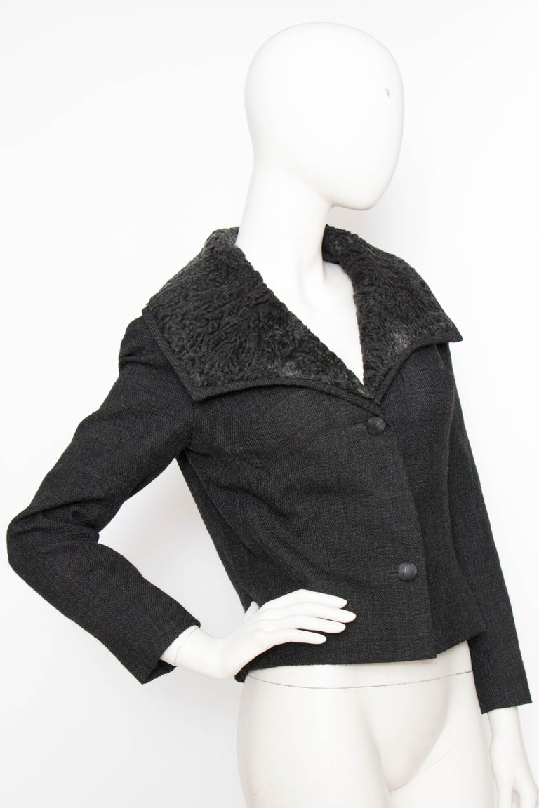 A 1950s cropped Christian Dior wool jacket with an elegant v-neckline, front-buttoned closure and fur-trimmed collar. The jacket is slightly nipped at the waist and has beautiful couture-style dart and seam work. The jacket is fully lined.  The size
