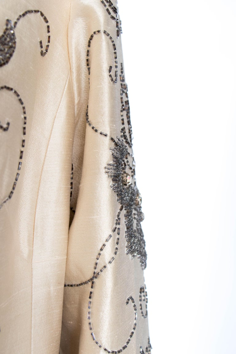 An incredible 1960s couture silk jacket with a round collar and a hidden front button closure. Intricate beading with silver beads and clear rhinestones are set in a floral pattern across the coat. The coat is fully lined.