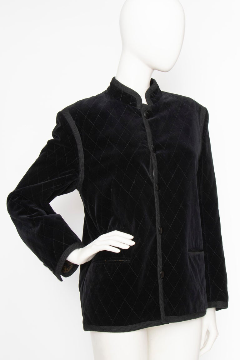 A 1970s Yves Saint Laurent Rive Gauche quilted black velvet jacket with a button-down front, side pockets and stand up collar. The jacket is fully lined and is completed by a braided cotton trim.  The size of the jacket corresponds to a modern size