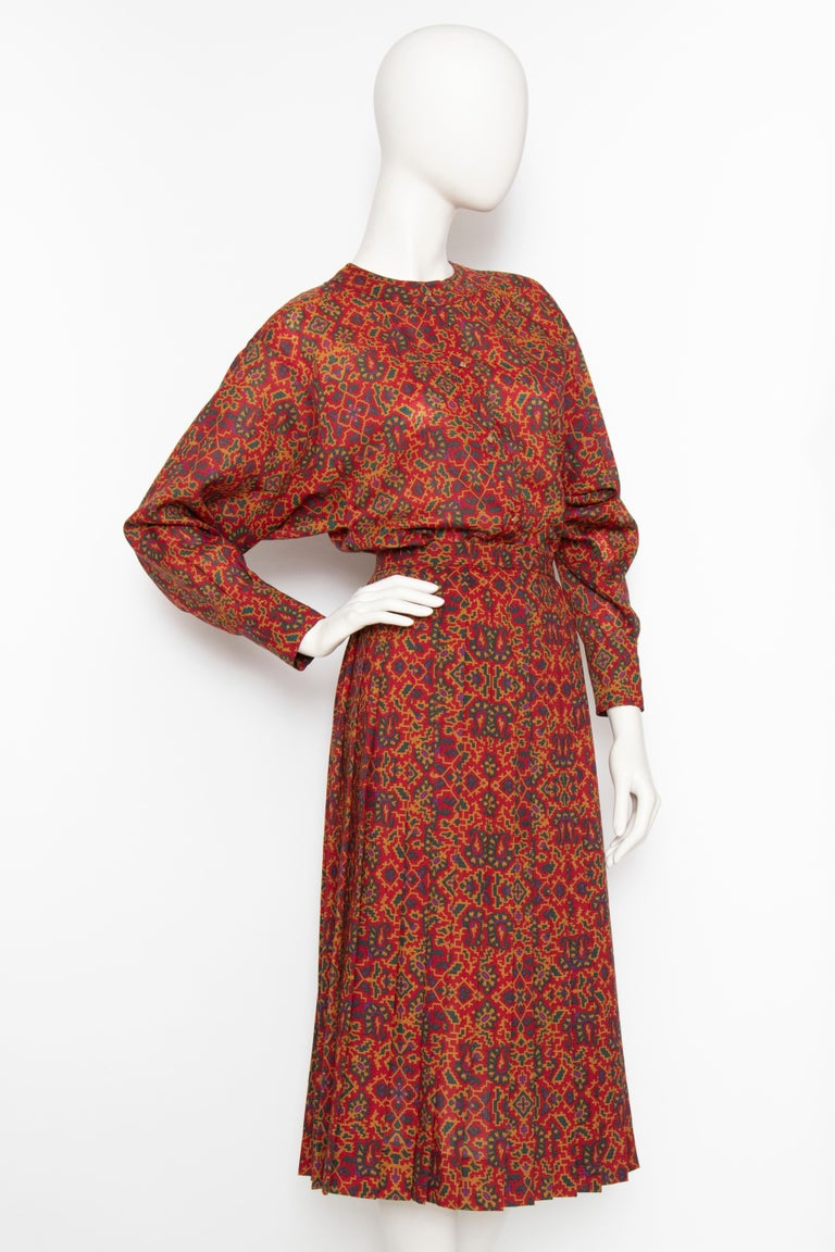 A late 1970s Yves Saint Laurent Rive Gauche red two-piece dress consisting of a pleated a-line skirt and collarless blouse. Both are unlined and feature a graphic print in classic YSL colours.   The size of the item corresponds to a modern size