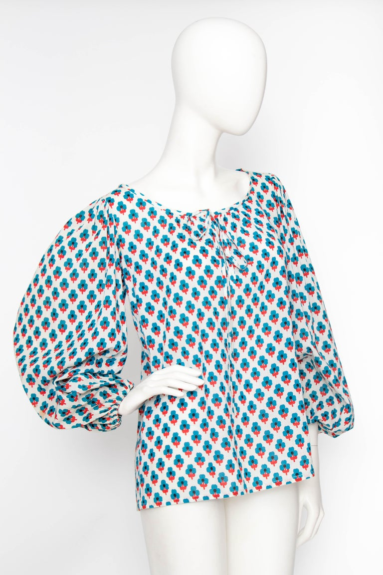 A 1970s Yves Saint Laurent Rive Gauche peasant blouse with a round neckline with drawstring detail and voluminous sleeves with elasticated cuffs. A fabulous floral print in red and blue adorn the white semi-sheer cotton.    The size of the blouse