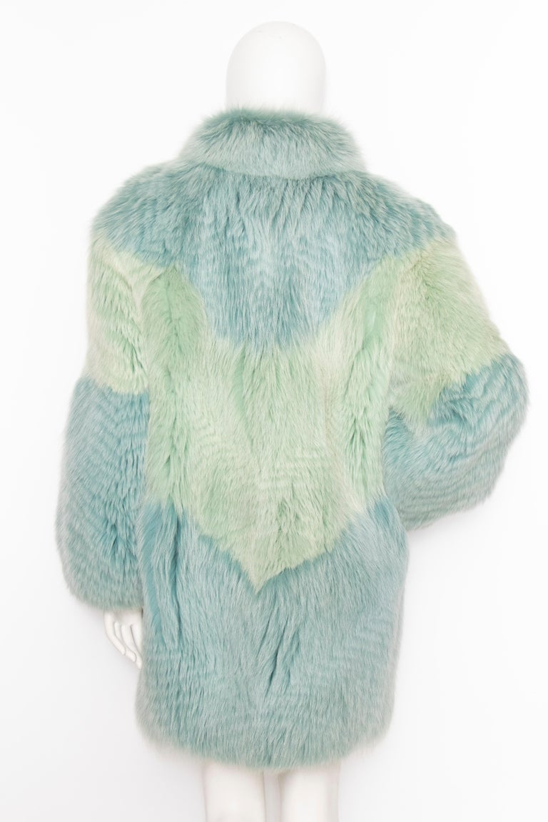 A fabulously extravagant 1980s dyed fox fur coat with great volume and hook closure in front. The stunning colour combines mint green and blue. The coat is fully lined and has side pockets.   The size of the coat corresponds to a modern size medium,