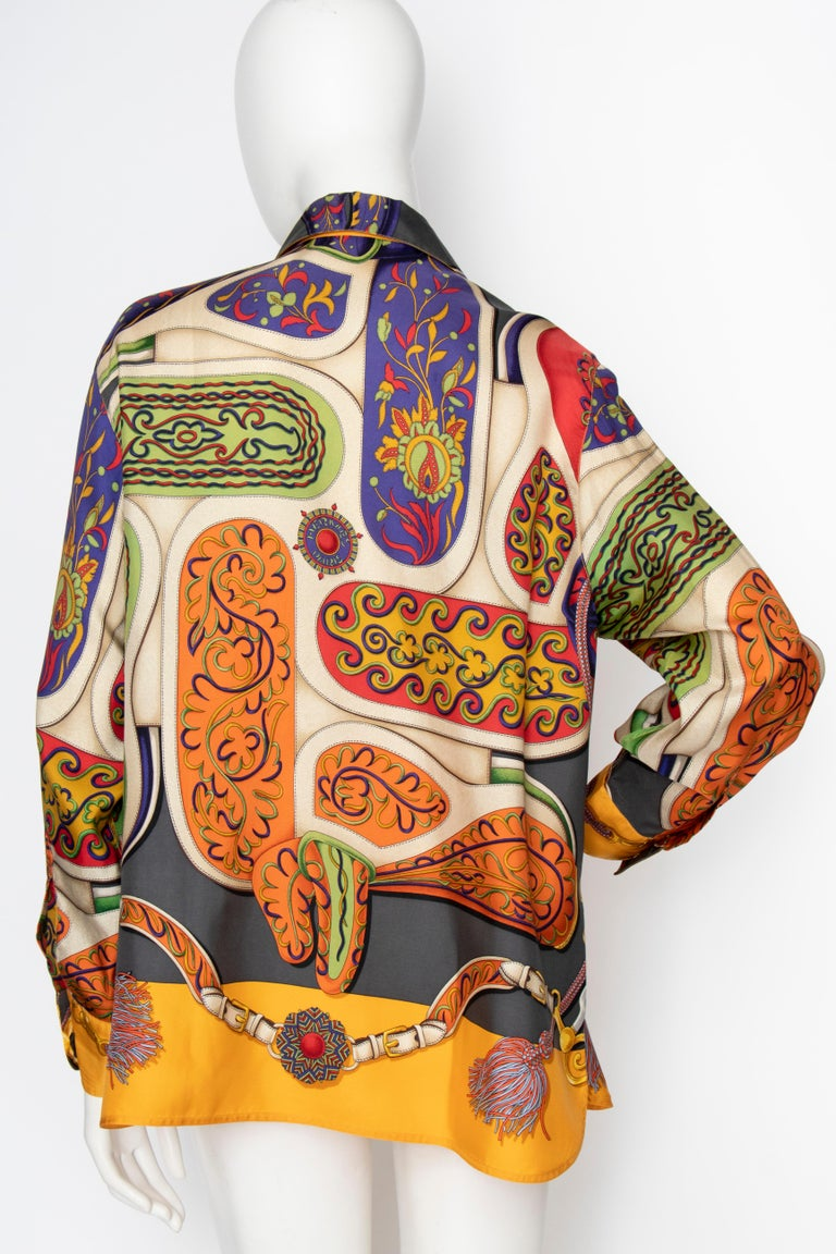 A 1980s Hermès Henri d'Origny silk print blouse with a buttoned-down front, Hermès engraved buttons and one-buttoned cuffs. The bold print is held in bright colours incorporating bold primary colours with white and black accents.  The size of the