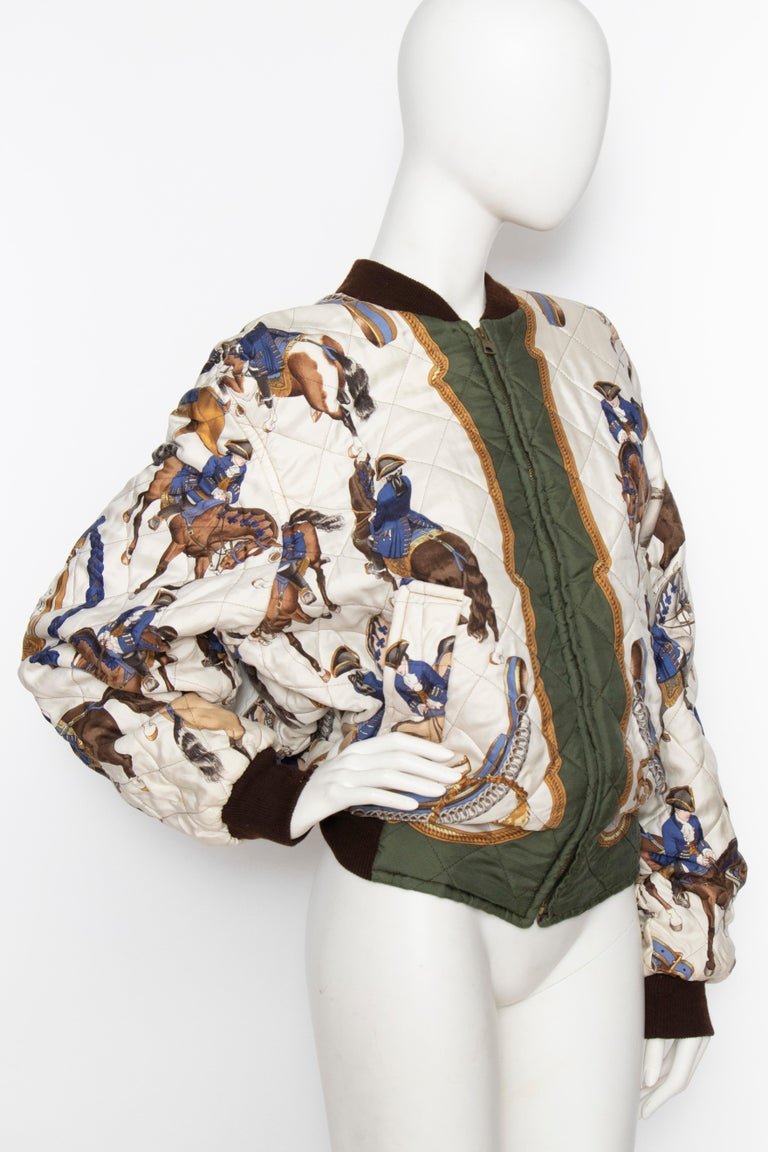 A 1980s reversible Hermès silk bomber jacket with a hunter green lining on one side and a white quilted on the other. The quilted side features a 'Reprise' motif. A brown elasticated cotton trim wrap around the collar and hemline.   The size of the