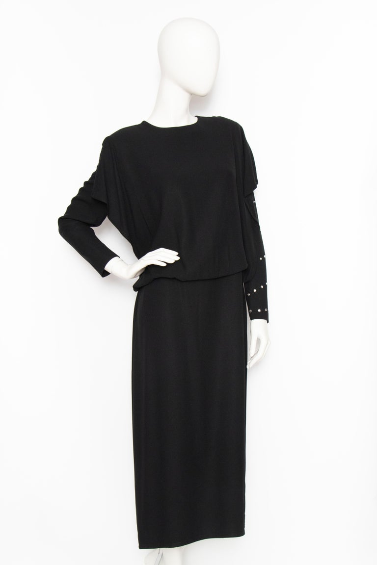 A 1980s Sonia Rykiel black viscose dress with a loosely fitted skirt and voluminous blouse with long sleeves. A single sleeve is encrusted with large rhinestones and the back has a push-button closure. The dress is unlined.   The size of the dress
