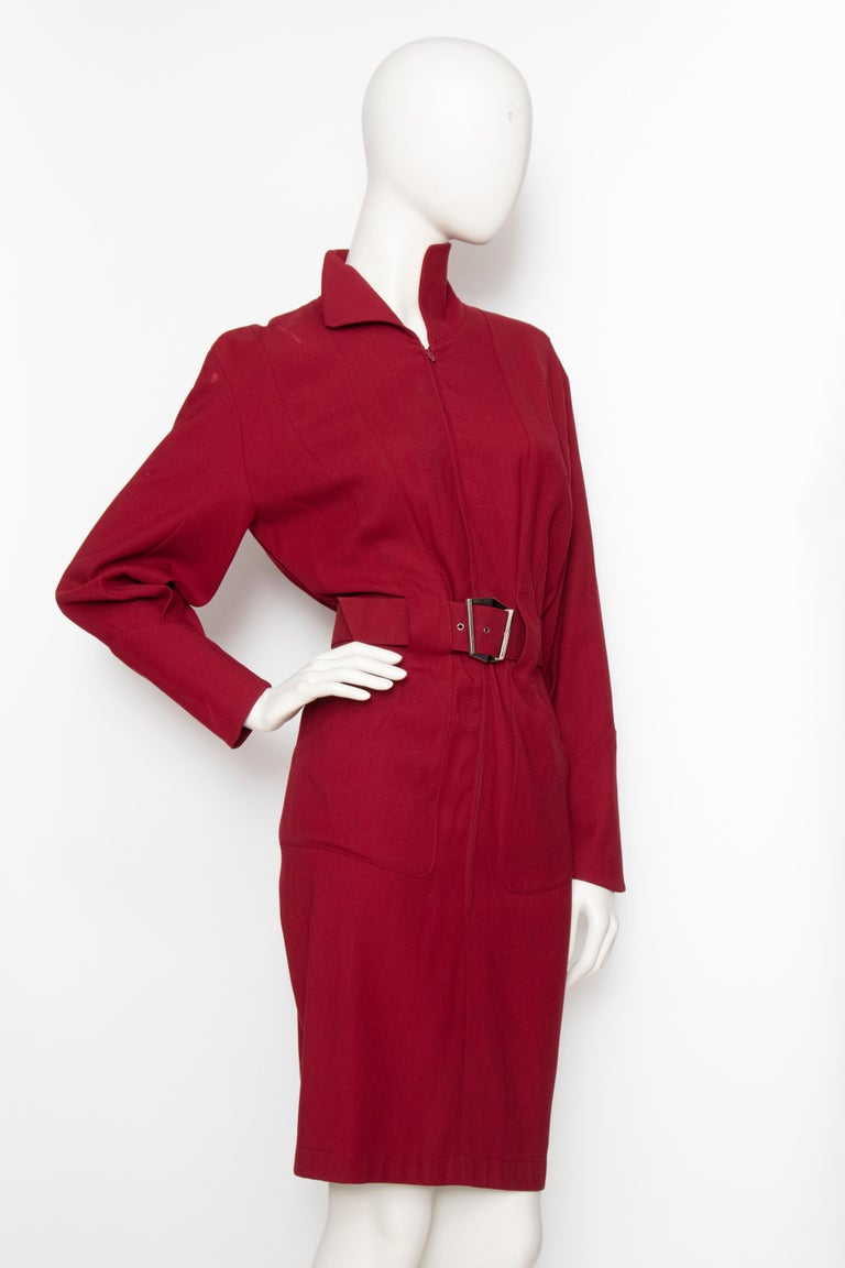 A fabulous 1980s Thierry Mugler wine red wool dress with a fitted wasp waist, pencil skirt and long sleeves with fitted cuffs. The dress is fully lined and has a matching waist belt with a characteristic graphic silver buckle.   The size of the