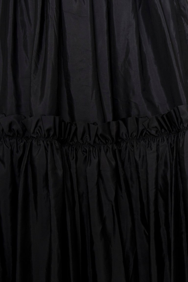 A 1980s Vintage Yves Saint Laurent Rive Gauche floor-length black silk taffeta skirt with a fitted waist, zipper closure and gorgeous ruffled trimmed layers. The skirt is unlined.   The size of the skirt corresponds to a modern size Small, but