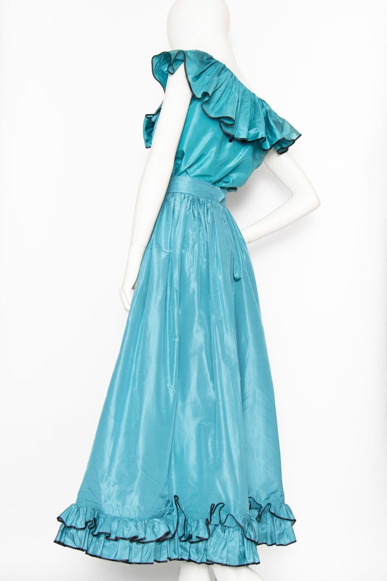 An incredible 1980s Yves Saint Laurent luscious teal blue silk taffeta two-piece dress consisting of a wide a-line skirt and sleeveless top. Both items have a ruffle detail, the skirt at the hem and the blouse at the collar complete with bow detail.