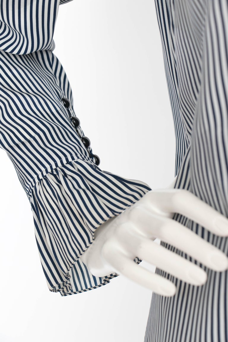 A 1980s Yves Saint Lauren blue and white stripe silk blouse with a ruffle collar and ruffle piping along each cuff. A subtle jacquard weave makes illusionist circles across the blouse.   The size of the blouse corresponds to a modern size small, but