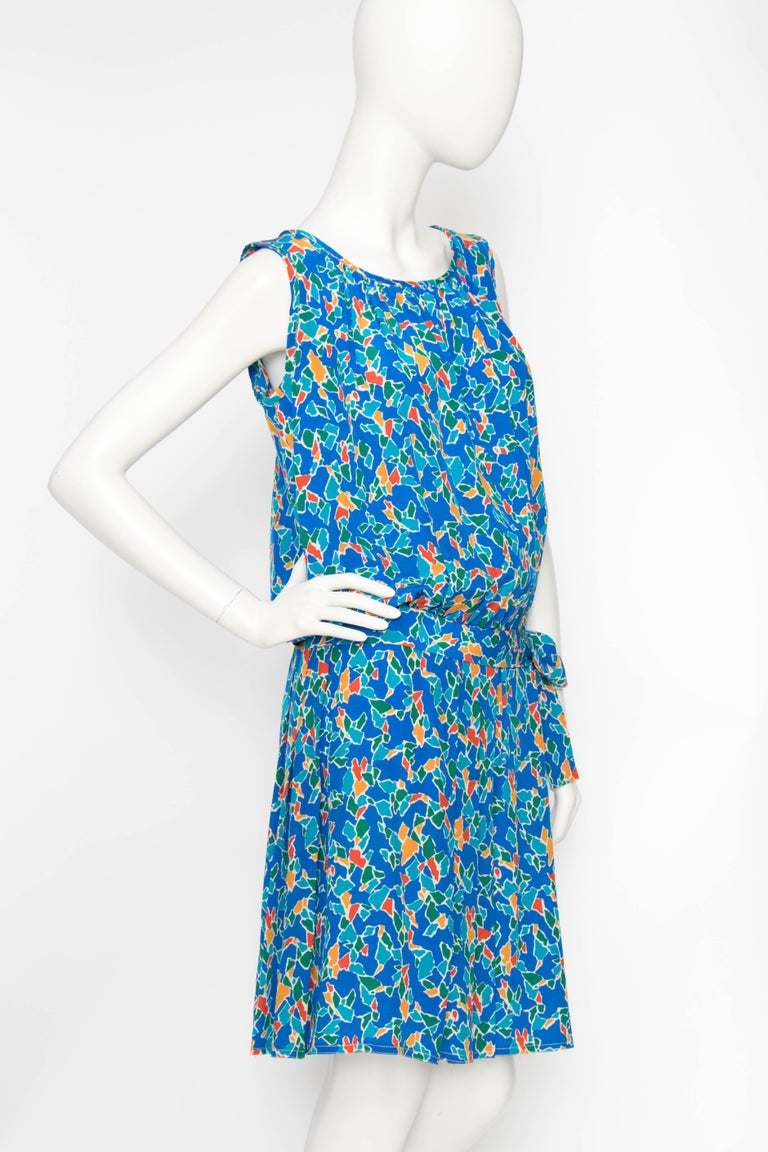 A 1980s Yves Saint Laurent Rive Gauche silk dress with a round neckline, pleated skirt and drop waist with bow detail. The sleeveless dress is clad in a fun graphic print in bold green, red, yellow and blue with white accents.   The size of the