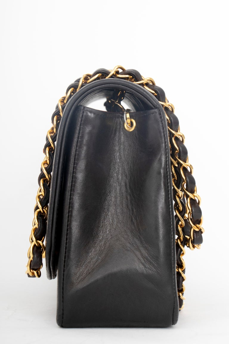 A 1990s Chanel black quilted lambskin shoulder bag with gold hardware.   The bag has the following measurements: Length: 25 cm Depth: 7.5 cm Hight: 15 cm