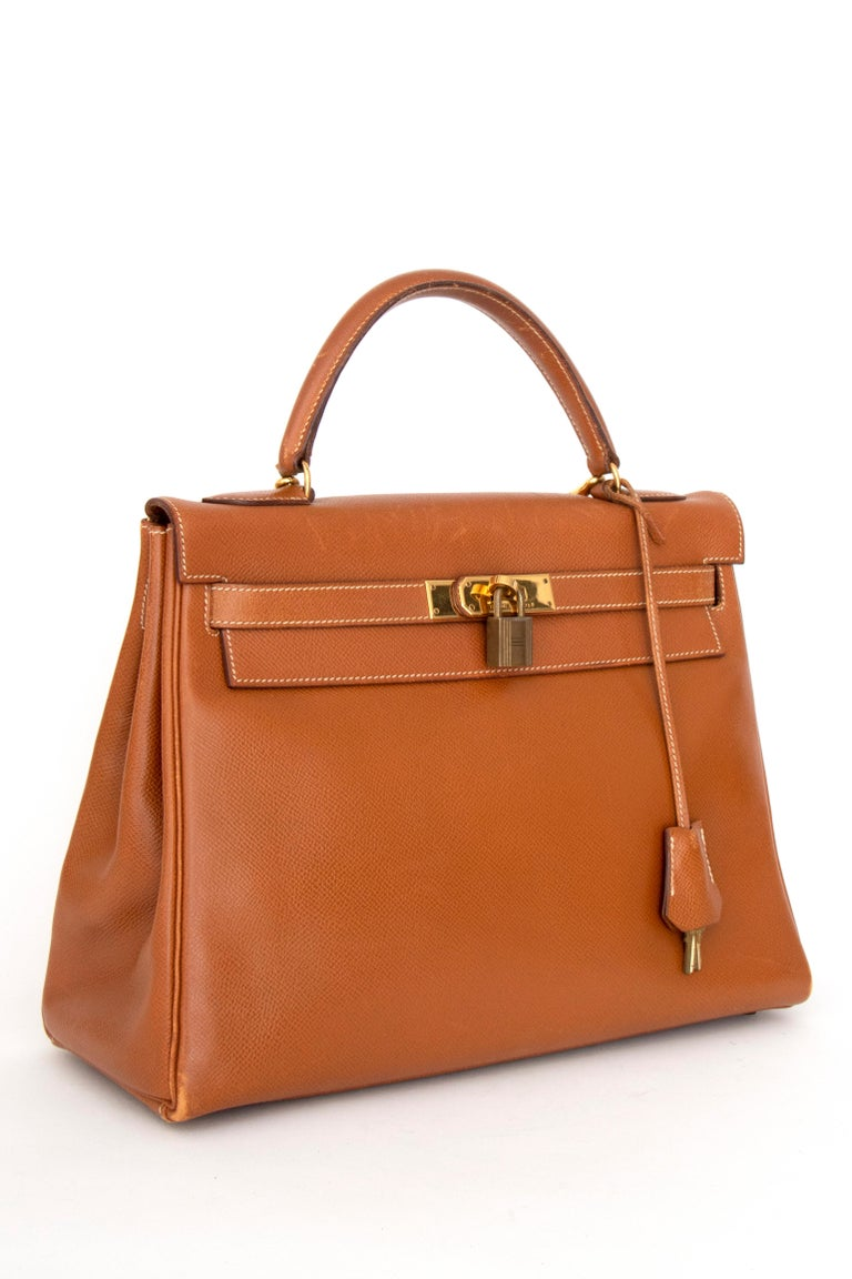 A 1990s vintage Hermès Kelly epsom handbag with gold hardware, a front toggle closure, lock and key, and a detachable strap for easier wear.  The bag has the following measurements: Height: 23 cm Width: 32 cm Depth: 12 cm  This is a vintage bag
