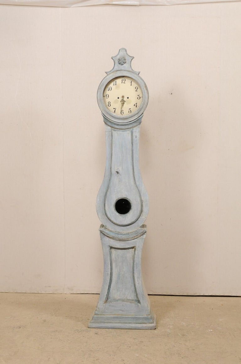 A Central Swedish 19th century long-case floor clock. This antique floor clock from central Sweden is crowned with an exaggerated carved crest atop it's head with delicate flower at center. Trimmed details accentuate it's neck and underside of the