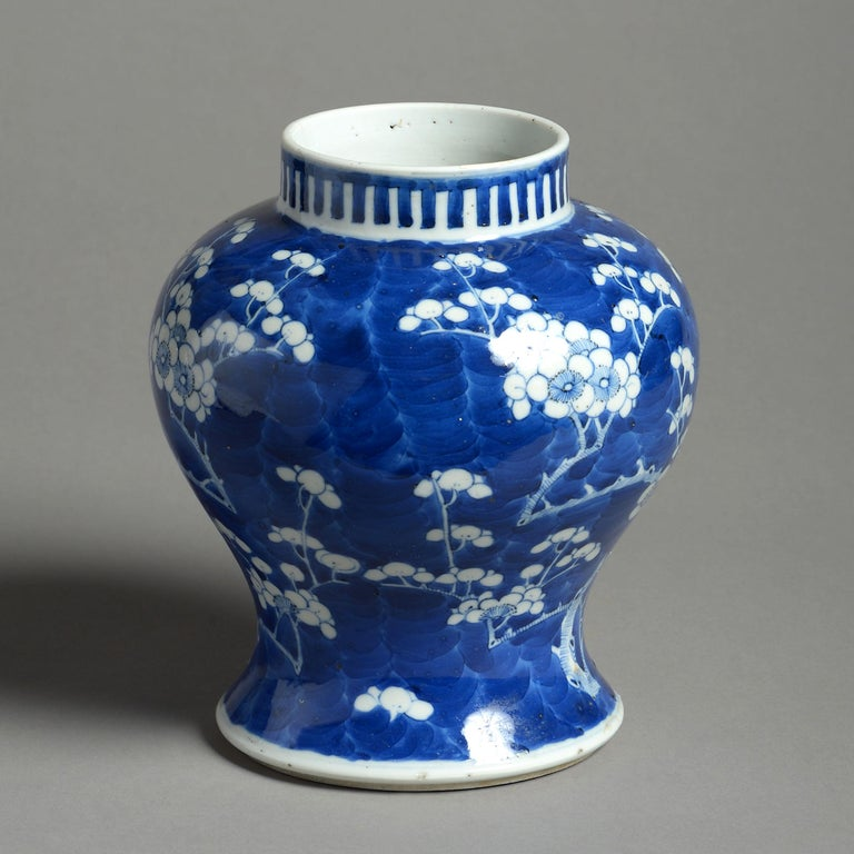 A mid-19th century porcelain baluster vase, decorated throughout with white prunus blossom upon a blue ground in the Kangxi manner.   Having four character marks to the underside. A hairline to the rim.