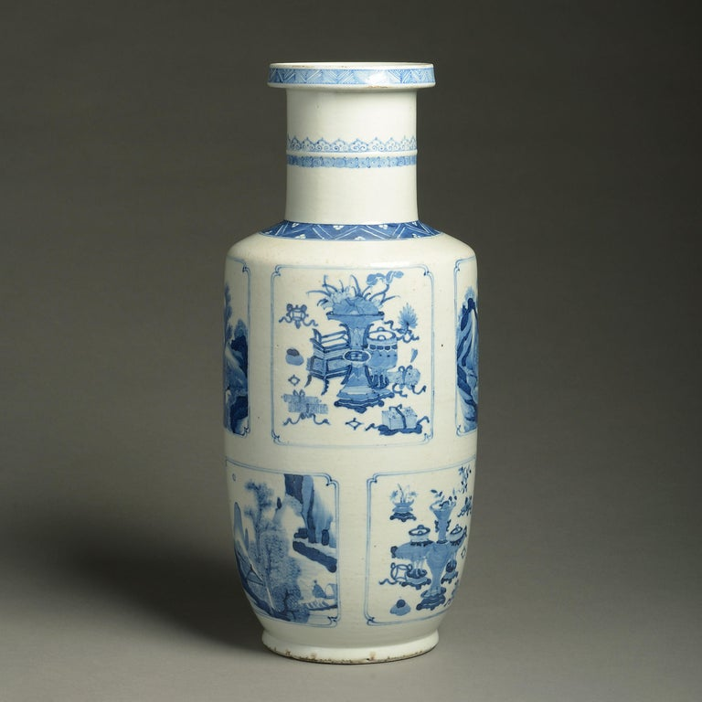 A 19th century blue and white porcelain rouleau vase, decorated throughout with panels depicting figurative scenes, landscapes and still life in the Kangxi manner. 