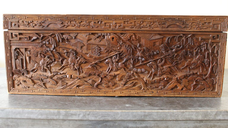 A 19th century Chinese carved camphor wood document box. The intricately carved box depicts the story of a warrior battle.  The document box showcases meticulous wooden dragon carved handles and Chinese key motifs.