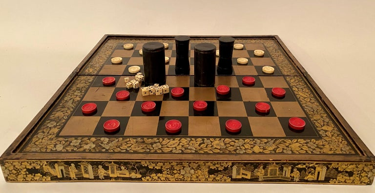 A 19th century Chinese export lacquer chess and backgammon board 50 cm x 50 cm with gold black lacquer board, with white and red counters and galloping dominoes.