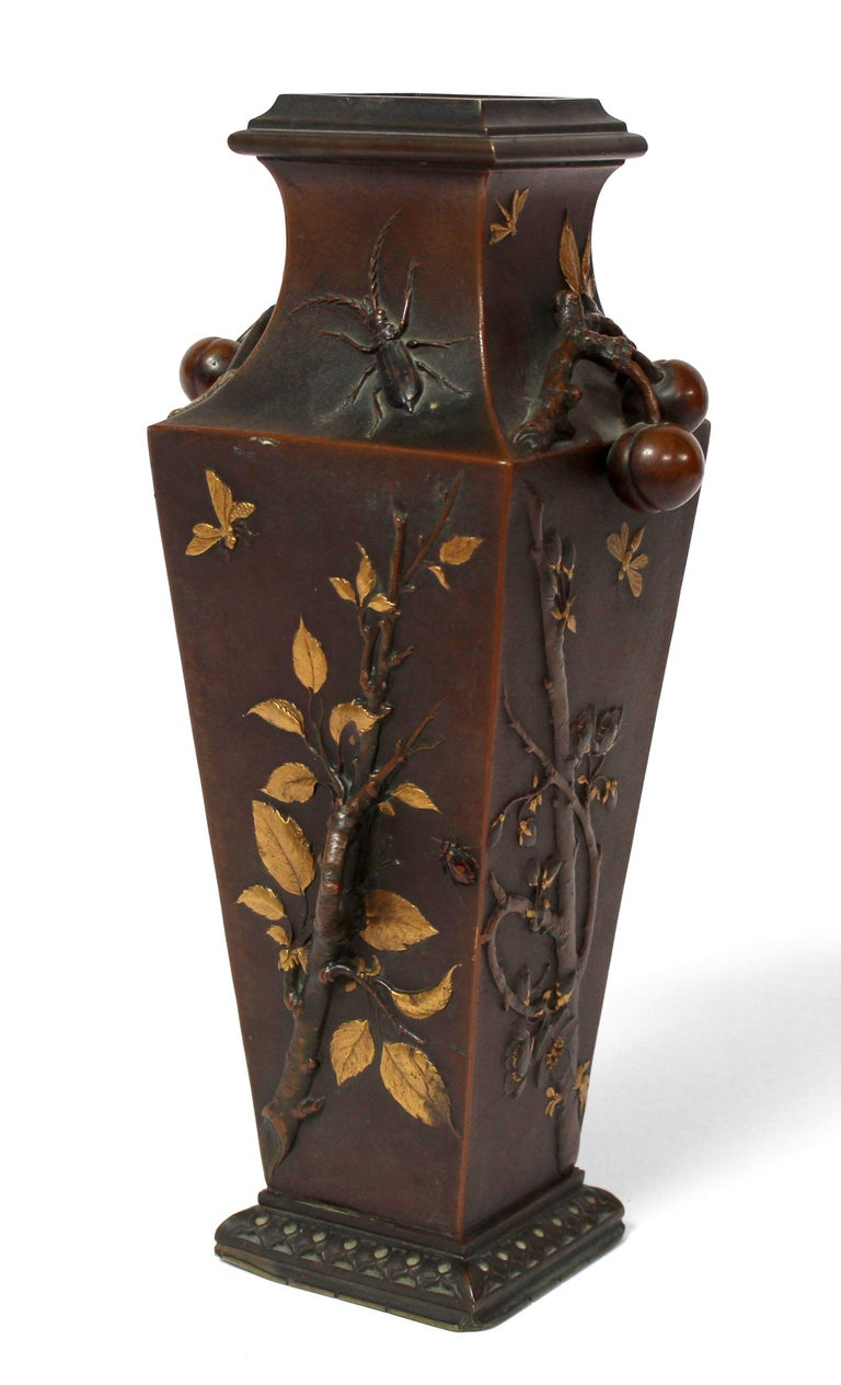 A French Japonisme bronze vase by Léopold Oudry, circa 1870 Bronze square-section baluster vase with brown and gold patina Relief decoration inspired by Japanese foliage, branches, and insects the handles in the shape of khakis retained by a