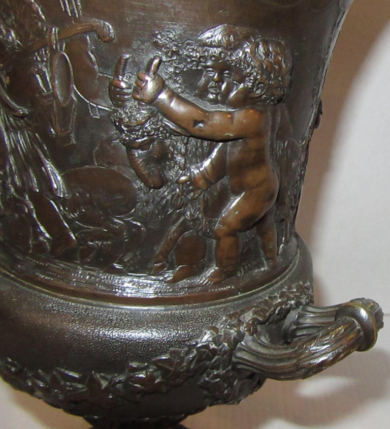 A campana form urn with twin handles, cast with frolicking putti and trailing ivy leaves. The basin seated on a spiral fluted foot over a square plinth. Stamped CLODION below one handle. From the collection of Lord Vincent Constantine at Cross Hall