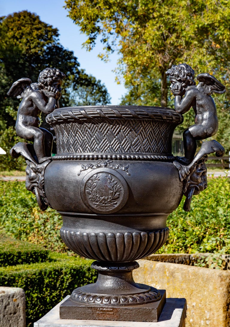A late 19th century French cast iron urn, cast by A. Durenne, after Claude Ballin I (1615-1678). The ovoid and part-lobed body with lattice border and flanked by twin putti handles and raised on a waisted socle and square plinth, the plinth stamped