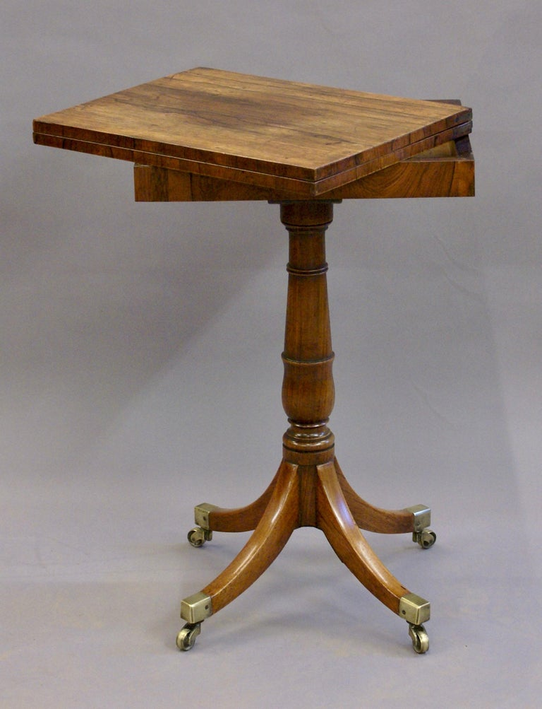 A Regency rosewood games table, in very good and original condition and of excellent colour and patina. Standing on patent, brass castors with out-swept legs supporting a turned central column. The swivel top, when open has lined velvet playing