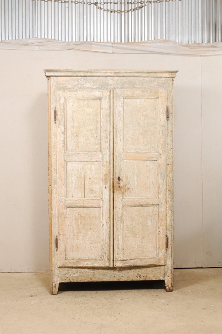 A French painted wood armoire storage cabinet from the early 19th century. This tall antique cabinet from the South of France features a molded cornice, a pair of three-panel doors which opens to reveal shelving for plentiful storage within, and is