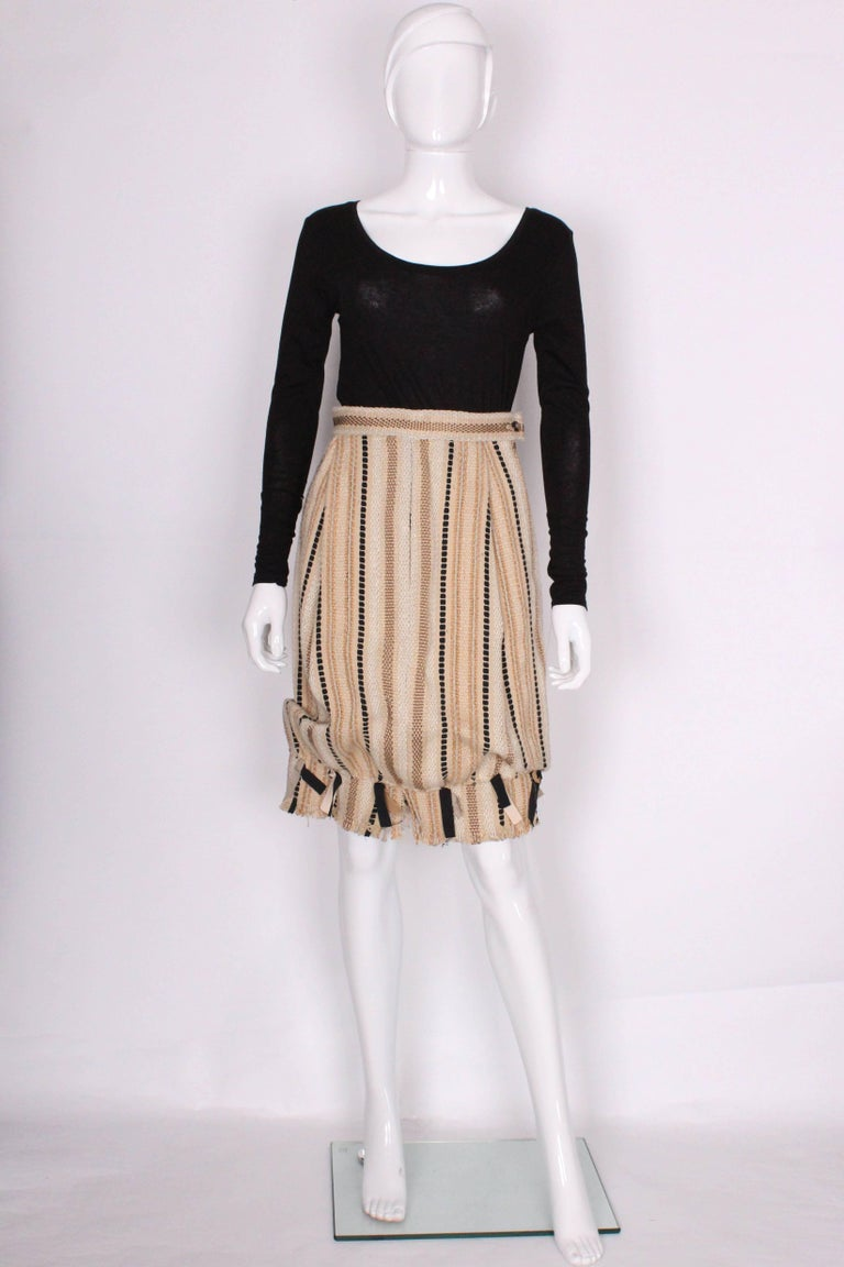 A great skirt by Yves Saint Laurent, Rive Gauche.This skirt is a bubble shape with a 3 1/2'' frill with ribbon detail at the hem. The fabric is a woven mix of linen, jute and acetate, in a biscuit colour background with gold, black and ivory