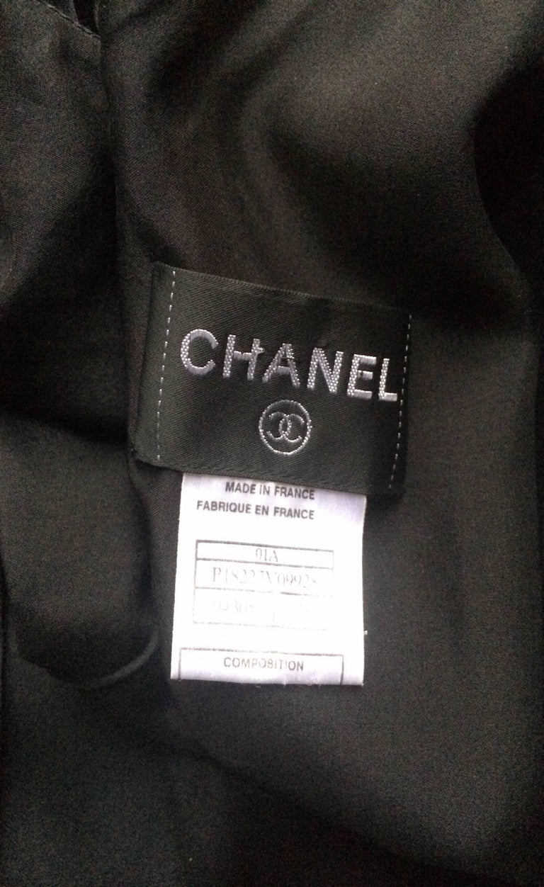 A fabulous 1990s black Chanel silk satin sleeveless cocktail dress with a nipped in waist and beautifully pleated skirt. The dress closes in the back with a row of Chanel double 'C' logo buttons.   This item is in overall very good vintage