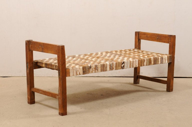 A Brazilian single woven-leather and wood daybed or bench. This Brazilian daybed from the mid-20th century has a great rustic feel with it's bucolic frame and leather strip seat. The wooden arms are comprised by a single straight board, raised