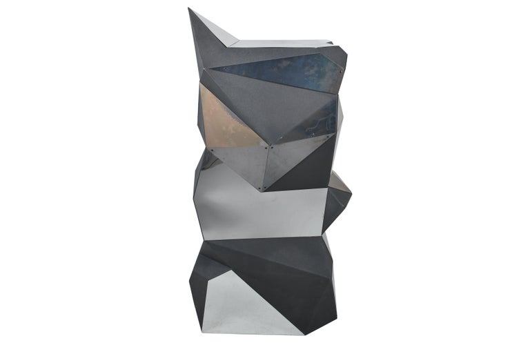 A quirky pedestal or object in black foam with plexi mirror shapes in triangular asymmetrical balance, forming a multifaceted curious object.