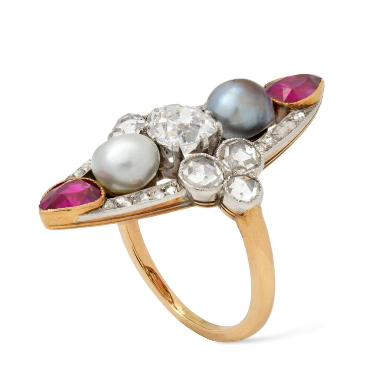 A Belle Epoque pearl, ruby and diamond navette-shaped ring, the old cushion-cut diamond estimated to weigh 0.8 carats, vertically set between a white and a grey pearl, accompanied by GCS Report stating to be of natural saltwater origin,