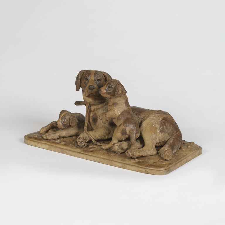 A 'Black Forest' Carved Dog Group Constructed in naturalistically carved and stained limewood, on a rectangular base with radiused angles, the bitch couchant, and attending to her two pups, all fitted with realistic glass eyes, in the manner of