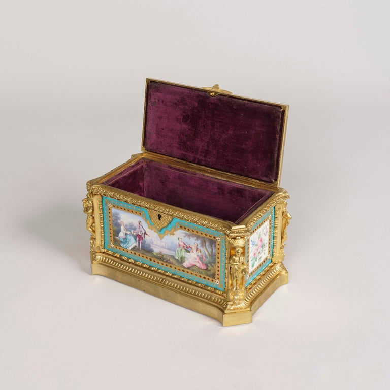 A jewel casket in the Louis XVI manner by Maison Tahan.  Constructed in gilt bronze, and adorned with 'Sevres' type porcelain hand painted polychrome panels on a Bleu Celeste background; of rectangular form, with everted angles, and figures