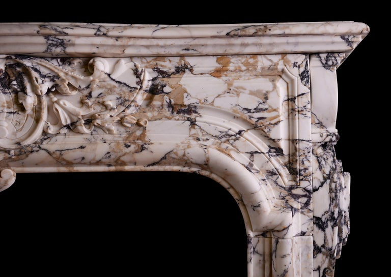 A Fine quality period French Louis XIV/XV transitional fireplace in Breche Violette marble. The moulded jambs with carved brackets to outgrounds. The arched, panelled frieze with cartouche to centre, flanked by foliage and scrollwork. Moulded shelf