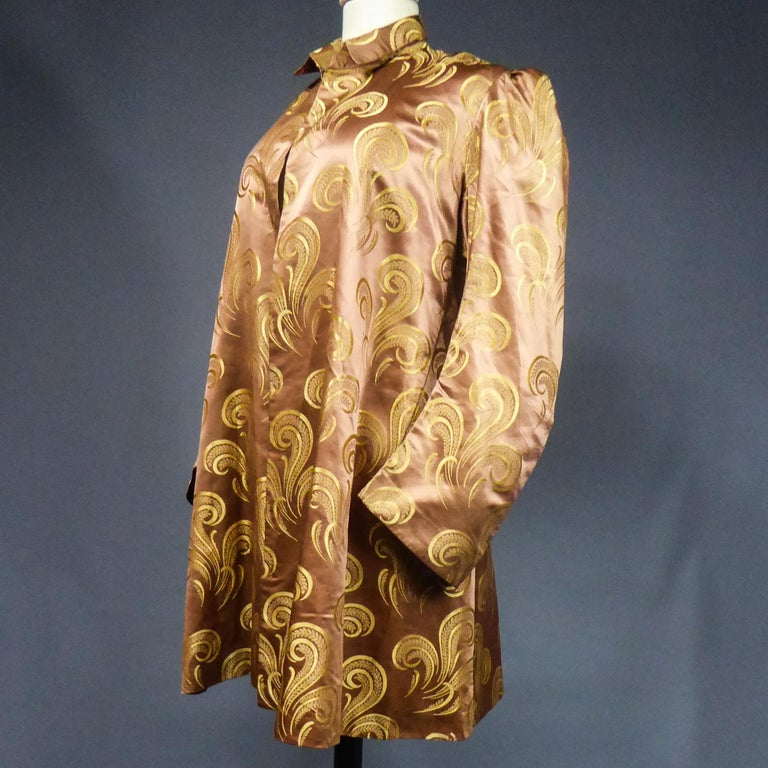 Circa 1930/1950 France  Amazing evening or party jacket inspired by Amazone style, in brown silk satin with gold stylized patterns in volutes, feathers and panaches. This is a reuse of an older dress because the Brocaded satin silk is to date
