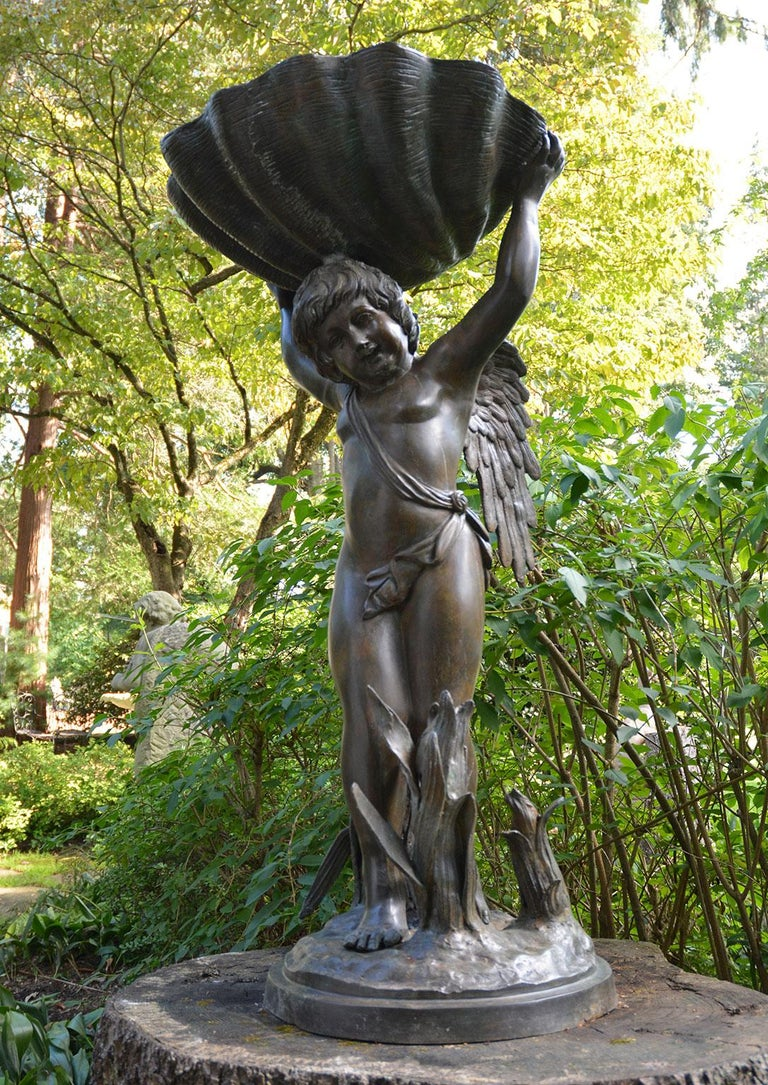 A bronze winged cherub fountain, semi-draped, standing supporting a large shell form bowl, his feet amidst tropical foliage on a round base. From a Baltimore, MD estate. Circular stone base not included.