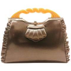 A brown leather handbag, with a carved amber Bakelite handle, English, 1930s