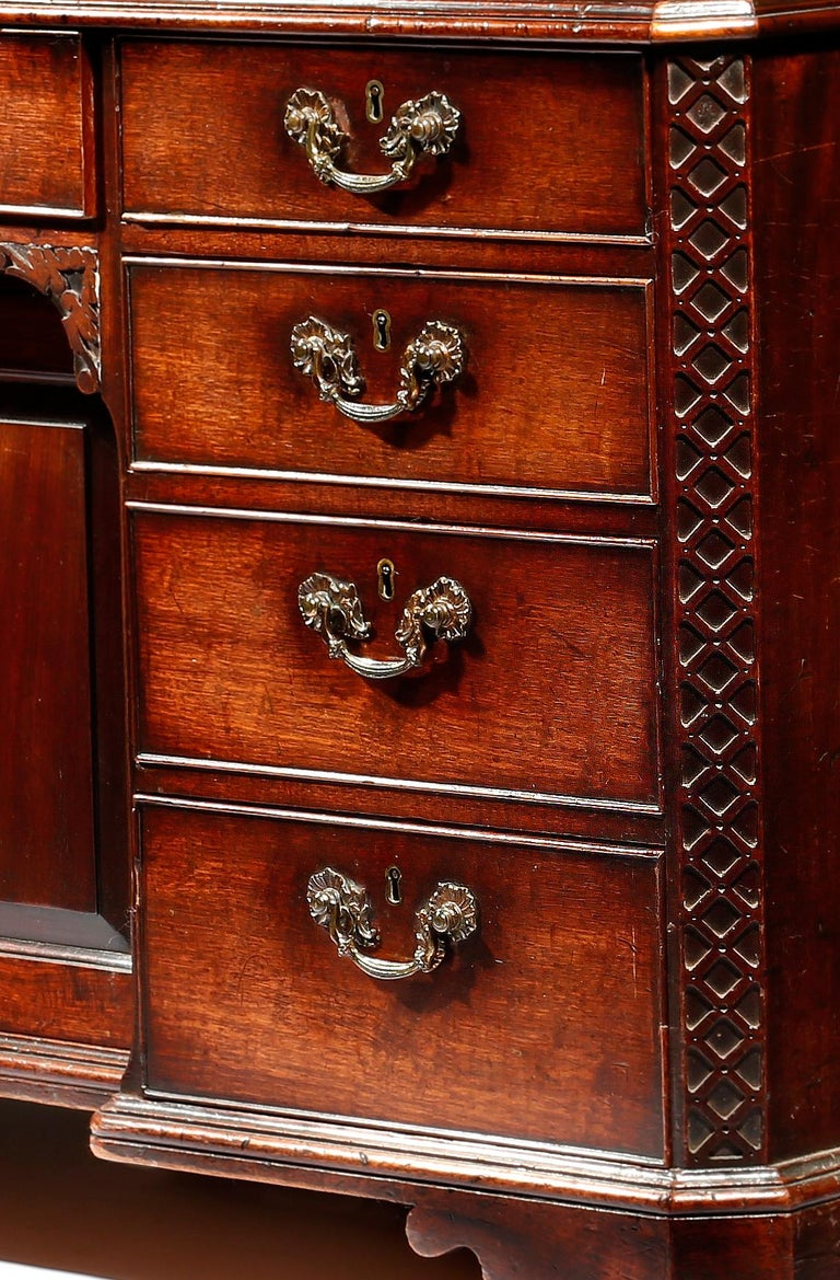 A George III Chippendale period mahogany knee-hole desk the well figured rectangular top with a thumb moulded edge, above banks of drawers, flanked by blind fret canted corners, resting on angled bracket feet, retaining its original brass handles,